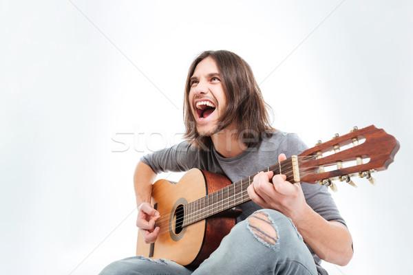 счастливым молодым человеком длинные волосы играет гитаре пения Сток-фото © deandrobot