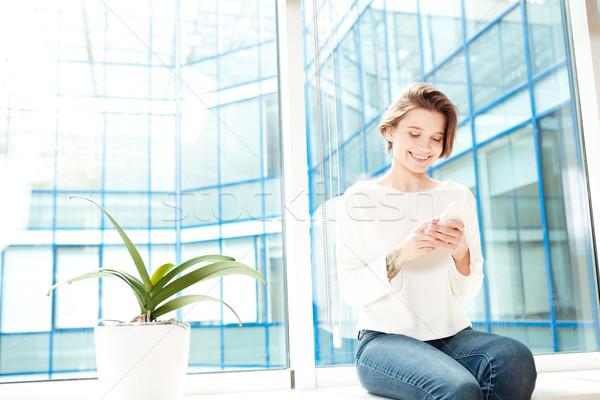 Donna seduta davanzale ufficio smartphone Foto d'archivio © deandrobot