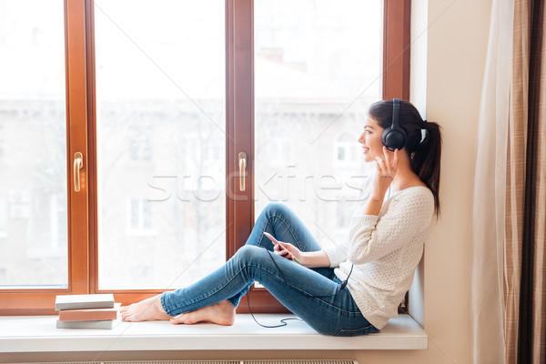 Gülümseyen kadın oturma pencere eşiği dinleme müzik kulaklık Stok fotoğraf © deandrobot