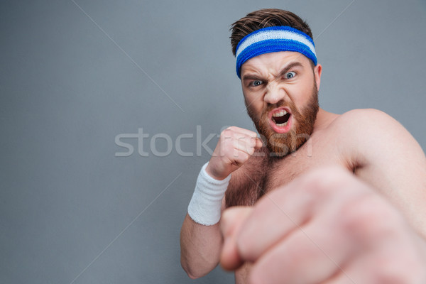 Mad irritated sportsman shouting and punching at camera with fist Stock photo © deandrobot
