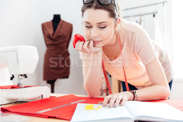 Concentrated woman seamstress using pattern and drawing on red fabric  Stock photo © deandrobot