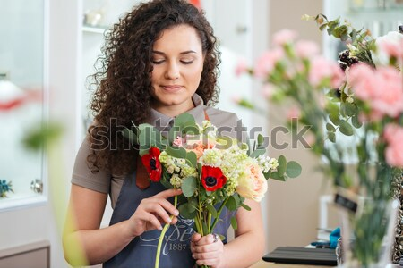 Lovely woman florist with bouquet of flowers working in shop Stock photo © deandrobot