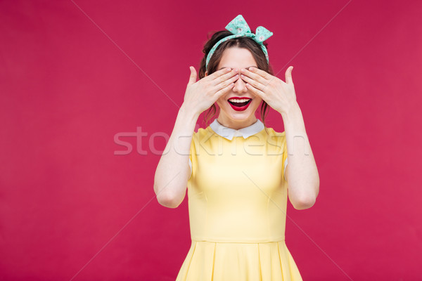 Happy attractive pinup girl covered her eyes by hands Stock photo © deandrobot