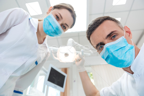 Two dentists making dental treatment to a patient Stock photo © deandrobot