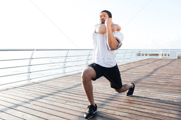 Serious sportsman stretching legs and arms at the sunrise Stock photo © deandrobot