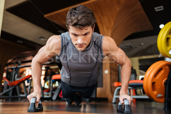 Man athlete training and doing push-ups in gym Stock photo © deandrobot