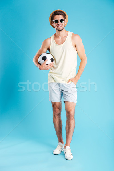 Stock photo: Smiling man in shorts, hat and sunglasses holding football ball