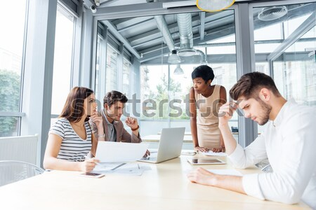 Happy woman standing and making presentation using flipchart in office Stock photo © deandrobot