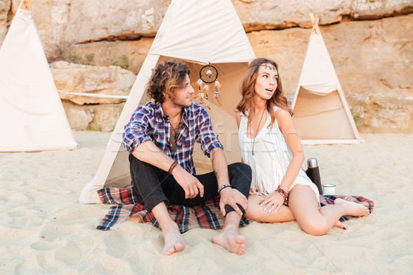 Couple sitting and looking away in teepee on the beach Stock photo © deandrobot