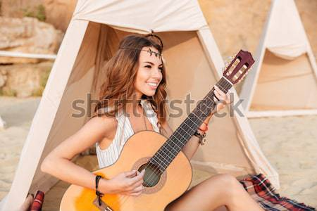 Thoughtful young woman with guitar in teepee on the beach Stock photo © deandrobot