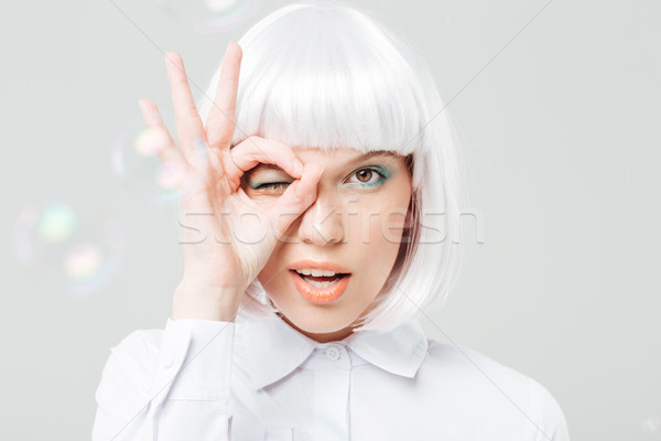 Playful charming young woman looking through her fingers Stock photo © deandrobot