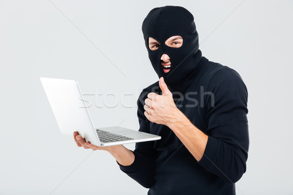 Man in balaclava using laptop and showing thumbs up Stock photo © deandrobot