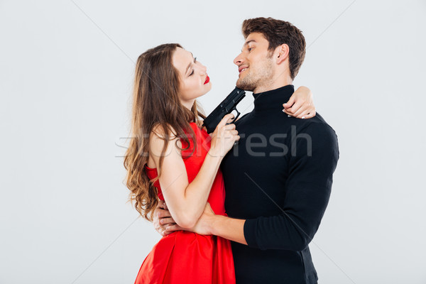 Happy young couple embracing and posing with gun Stock photo © deandrobot
