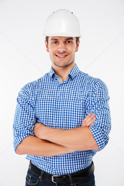 Happy man builder in hard hat standing with arms crossed Stock photo © deandrobot
