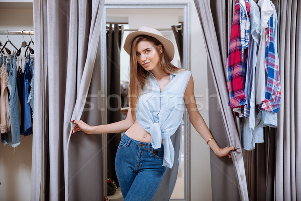 Beautiful young woman in dressing room of clothing shop Stock photo © deandrobot
