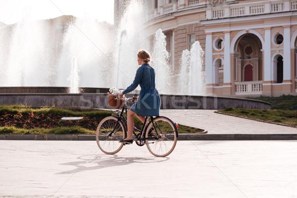 Pretty young woman riding a bike near fountain Stock photo © deandrobot