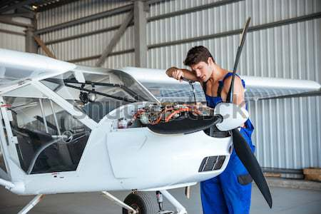 Handsome young repair man fixing plane engine Stock photo © deandrobot