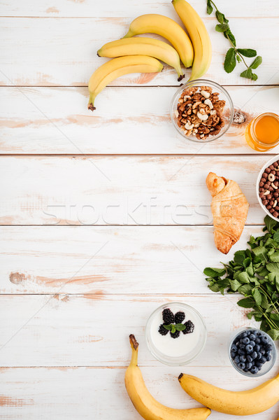 Bananas, berries, croissant, walnuts mint and honey on wooden background Stock photo © deandrobot