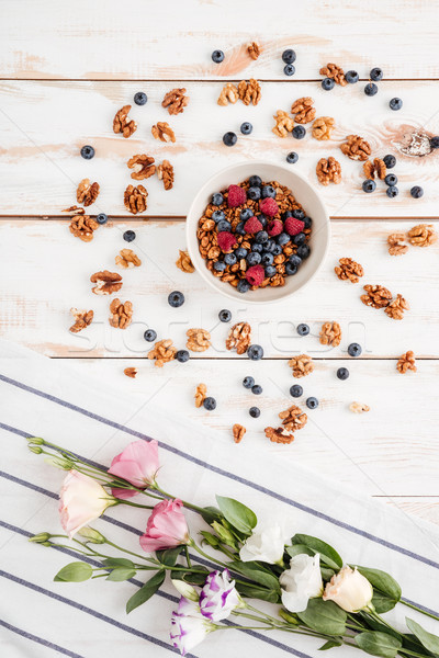 Flowers, napkin, cereals with berries and nuts on wooden background Stock photo © deandrobot