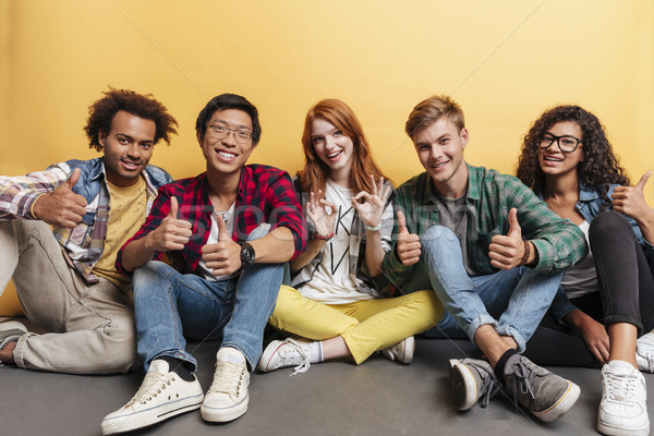 Multiethnic group of cheerful people sitting and showing thumbs up Stock photo © deandrobot