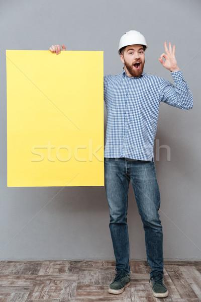 Happy builder holding copyspace board make okay gesture Stock photo © deandrobot