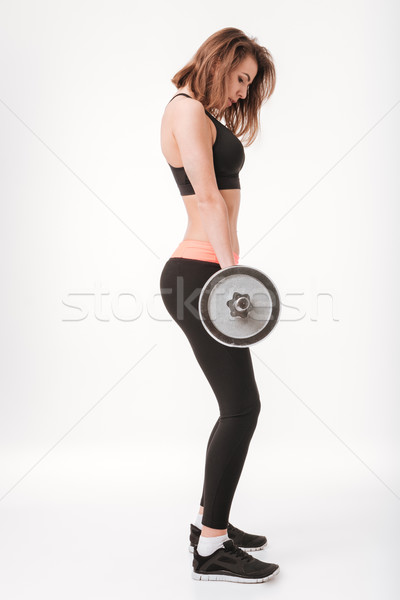 Beautiful young fitness lady make exercises with barbell Stock photo © deandrobot