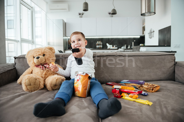 Cheerful boy sitting on sofa with teddy bear at home Stock photo © deandrobot