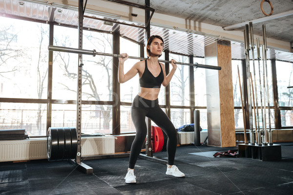 Sportswoman standing and working out in gym Stock photo © deandrobot