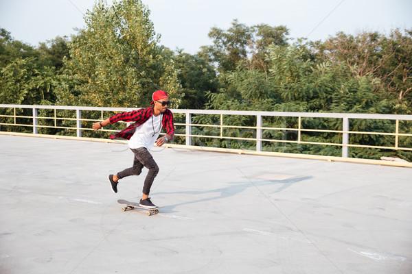 Attractive dark skinned man skateboarding Stock photo © deandrobot