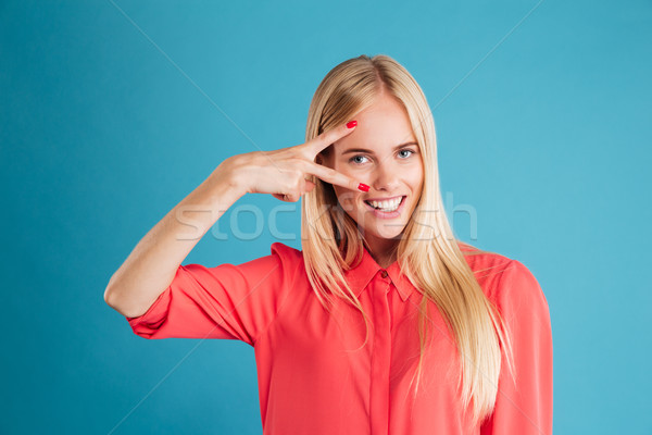 Portre genç gülümseyen kadın barış imzalamak Stok fotoğraf © deandrobot
