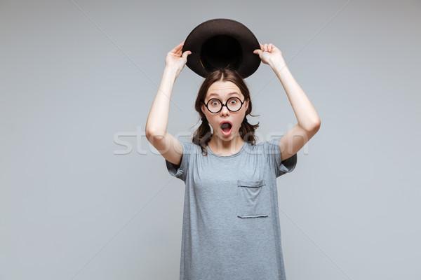 Shocked Female nerd holding overhead her hat Stock photo © deandrobot