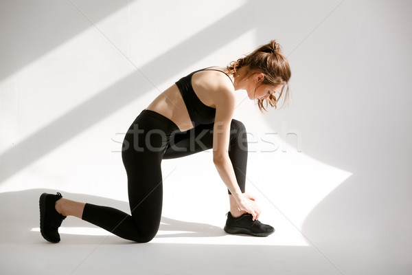 Young healthy sporty woman sitting on on knee Stock photo © deandrobot