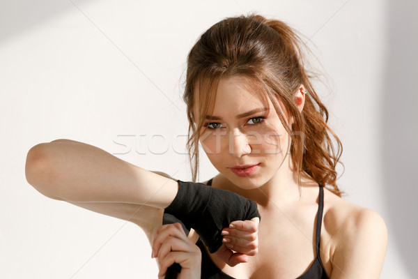 Portrait of a fitness woman wraping her hand with bandage Stock photo © deandrobot