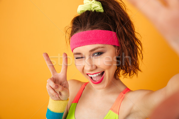 Smiling fitness woman taking selfie, winking and showing peace sign Stock photo © deandrobot