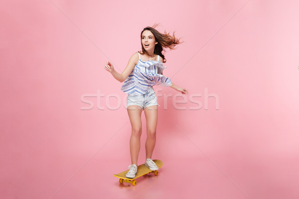 Full length of happy carefree young woman riding on skateboard Stock photo © deandrobot