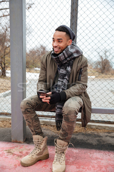 Happy african young man using cell phone outdoors in autumn Stock photo © deandrobot