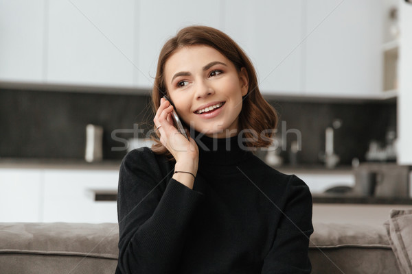Happy woman sitting at kitchen talking with phone Stock photo © deandrobot