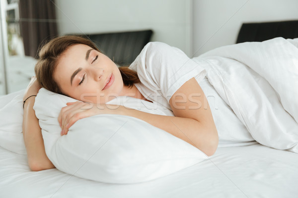 Amazing woman lies in bed at home indoors. Stock photo © deandrobot
