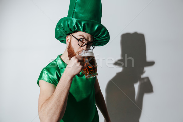 Serious man in st.patriks costume drinking beer Stock photo © deandrobot