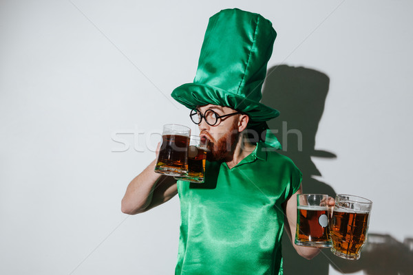 Funny man in st.patriks costume drinking beer from two cups Stock photo © deandrobot