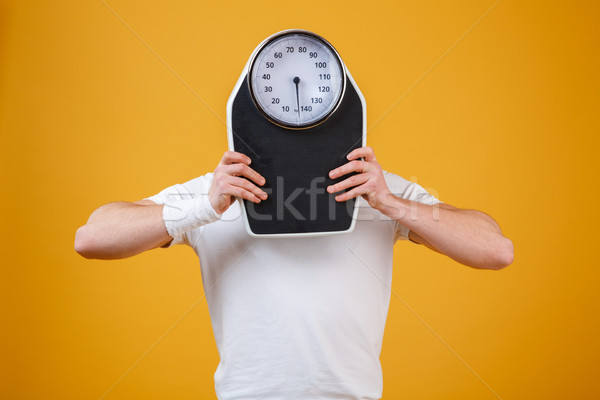 Young sports man hiding face behind weight scales Stock photo © deandrobot