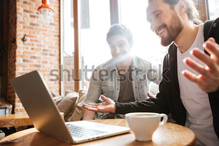 Side view of Friends with laptop in cafe Stock photo © deandrobot