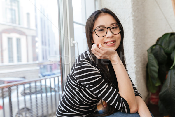 Side view of Smiling Asian woman sitting on windowsill Stock photo © deandrobot