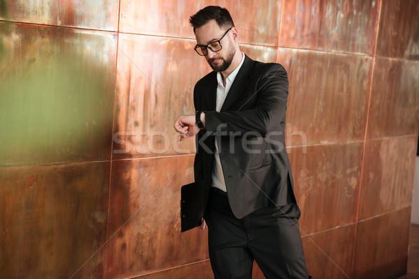 Business man looking at wristwatch Stock photo © deandrobot