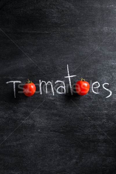 Image of tomatoes over dark background Stock photo © deandrobot