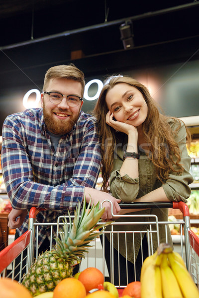 Smiling Loving couple standing near the shopping trolley Stock photo © deandrobot