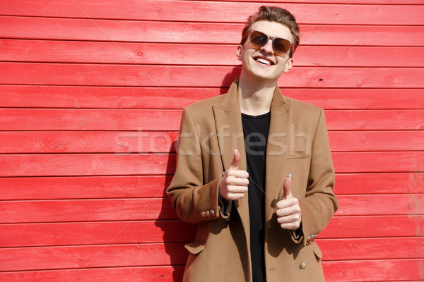 Happy young man in sunglasses standing and showing thumbs up Stock photo © deandrobot