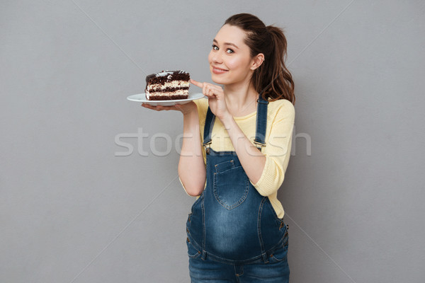 Smiling young pregnant woman holding plate with chocolate cake Stock photo © deandrobot