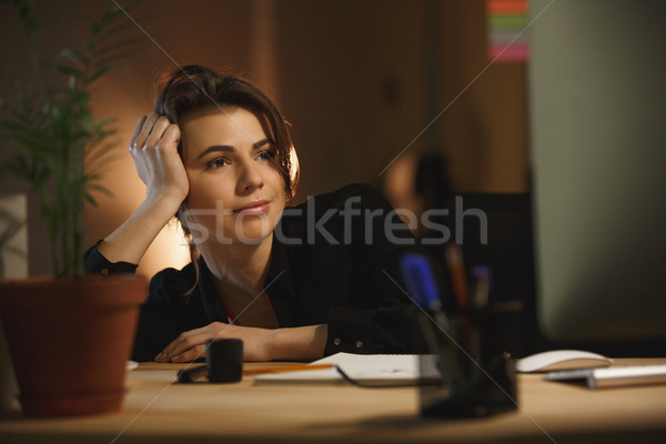 Concentrated young woman designer sitting in office at night Stock photo © deandrobot