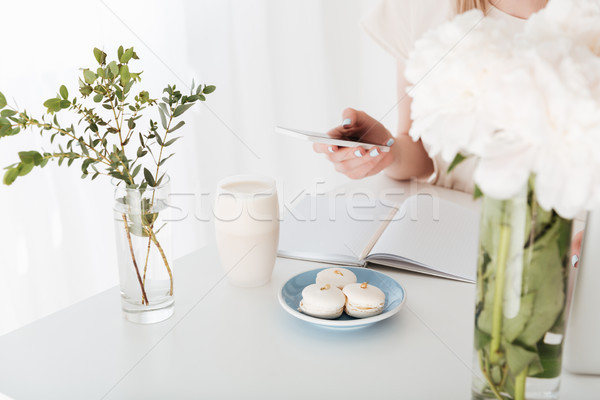 Cropped image of young woman sitting indoors make photo Stock photo © deandrobot
